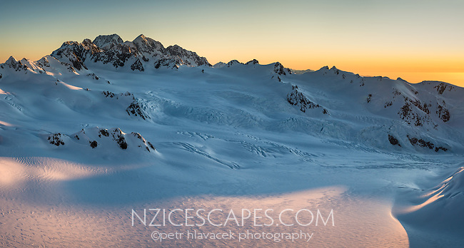 Vast area of Geikie Snowfield of upper parts of Franz Josef Glacier during setting sun with Mt. Tasman and Aoraki, Mount Cook dominating skyline, Westland Tai Poutini National Park, West Coast, UNESCO World Heritage Area, New Zealand, NZ