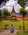A tourist ponders one of the shrines in the gardens at the Hindu temple of Ulun Danu at Candikuning on Bali, Indonesia.  Located in the high hills of the Bedugul, about 30 miles north of Bali's capital city of Denpasar, the temple is built on the shores of the crater Lake Bratan (formed from the sunken crater of a long-dormant volcano).  Much of the inner precincts of the temple is closed to the (non-Hindu) public, but the gardens are spectacular and feature fabulous shrines, statuary, and views.  (HDR Image)
