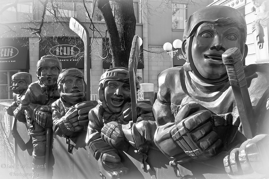 A black and white view of the Our Game bronze statue outside the Hockey Hall of Fame in Toronto