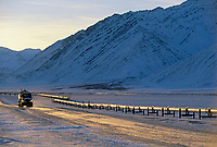 The Trans Alaska oil pipeline, truck on the James Dalton Highway (haul road) Atigun canyon, Brooks range, Arctic, Alaska.