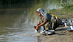 A woman washes dishes in a stream near her home in a village in Pakistan.