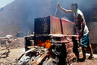 A Brazilian boy controls the slow boiling process in the metal tank loaded with shrimps on the yard of a dried shrimp manufacure in Pontal do Peba, Brazil, 13 March 2004.