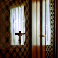 A crucifix stands on a window sill seen through doors in a religious building.