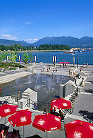 """Mill Marine Bistro - an Outdoor Restaurant Cafe with Red Sun Umbrellas - and Children playing at Water Park, along Waterfront at """"Coal Harbour"""", in the """"West End"""" of Vancouver, British Columbia, Canada, in Summer.  The North Shore Mountains (Coast Mountains) rise in the background."""
