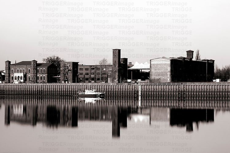 The photograph of an old industrial site on the river Elbe in Wittenberge with a passing police boat.