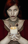 A girl with red hair holding a candle wearing a chain necklace looking at camera