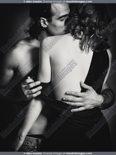Sensual portrait of a young sexy couple. Man with bare torso kissing a woman in a dress with open low back. Black and white.