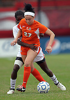 COLLEGE PARK, MD - OCTOBER 28, 2012:  Shade Pratt (22) of the University of Maryland holds onto Ally Andreini (27) of Miami during an ACC  women's tournament 1st. round match at Ludwig Field in College Park, MD. on October 28. Maryland won 2-1 on a golden goal in extra time.