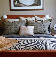A framed print hangs above a bed covered in contrasting fabrics and patterns