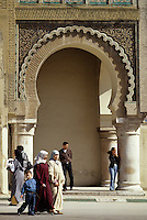Meknes, Morocco.  Left Archway of the Bab Mansour, built 1672-1732.  Entrance to the kasbah, the imperial quarter.  Women wearing typical traditional female dress.