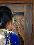A woman prepares herself for the Hindu festival of Maha Shivratri in Salang, a village in the Dhading District of Nepal.
