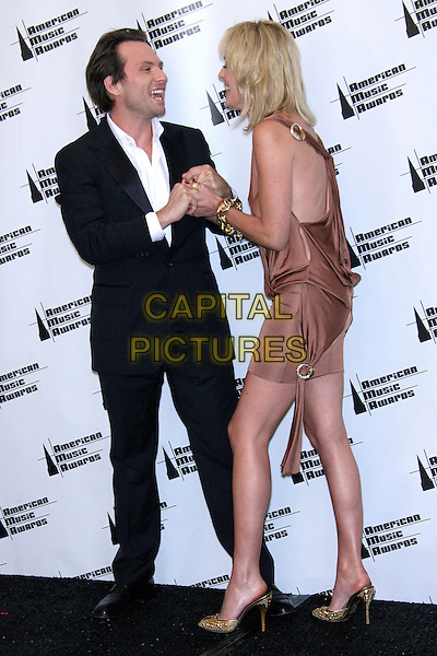 CHRISTIAN SLATER & SHARON STONE.34th Annual American Music Awards - Press Room held at the Shrine Auditorium, Los Angeles, California, USA..November 21st, 2006.full length black suit pink tan beige gold shoes dress wrap holding hands.CAP/ADM/ZL.©Zach Lipp/AdMedia/Capital Pictures
