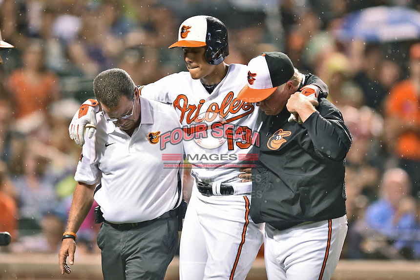 Baltimore Orioles third baseman Manny Machado #13 helped off the field by manager Buck Showalter #26 and head athletic trainer Richie Bancells during a game against the New York Yankees at Oriole Park at Camden Yards August 11, 2014 in Baltimore, Maryland. The Orioles defeated the Yankees 11-3. (Tony Farlow/Four Seam Images)