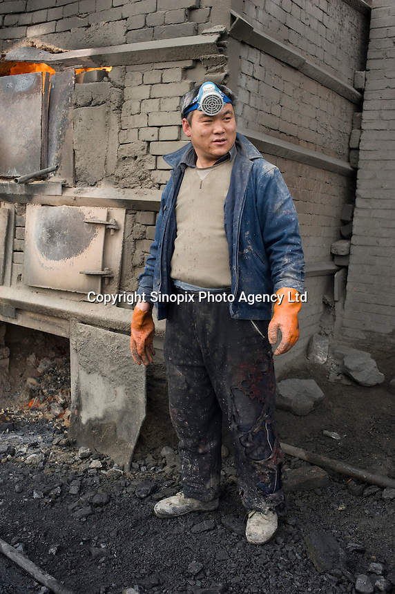 """A worker whose trousers have been shredded by acid at a private """"rare earth"""" processing plant in Guyan County about 60 km from Bayan Obo, Inner Mongolia. China produces accounts for some 97% of rare earth consumed world-wide. The """"rare earth elements"""" are a group of 17 elements that are essential in 25% of modern technology including cell phones, computer hard discs, and electric motors and inparticular green technology such as electric batteries and wind turbines. China yesterday, 23 September 2010, stopped trading rare earth with Japan, who rely on Chinese imports for its high tech industry,  over a territorial dispute. .."""