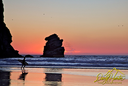 A surfer at sunset hurries out to catch a few waves before dark