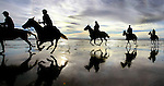 A group of riders enjoy a nice gallop at sunset along the Oregon Coast near Manzanita.