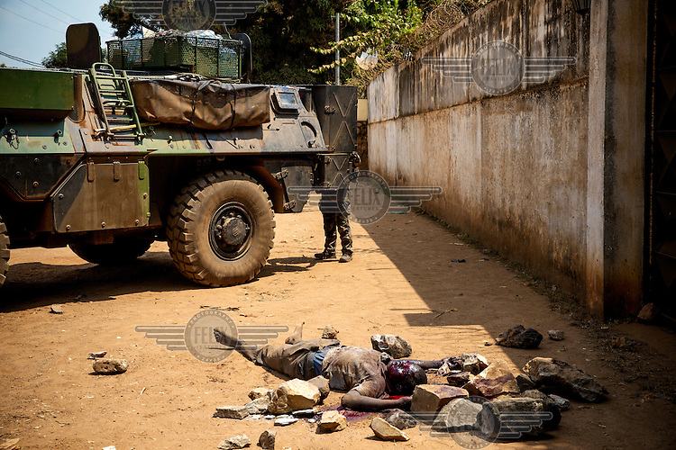 The body of a man lies in the road beside an French amoured vehicle. The man was accused of being a Seleka rebel. In 2013 a rebellion by a predominantly Muslim rebel group Seleka, led by Michel Djotodia, toppled the government of President Francios Bozize. Djotodia declared that Seleka would be disbanded but as law and order collapsed the ex-Seleka fighters roamed the country committing atrocities against the civilian population. In response a vigillante group, calling themselves Anti-Balaka (Anti-Machete), sought to defend their lives and property but they then began to take reprisals against the Muslim population and the conflict became increasingly sectarian. French and Chadian peacekeeping forces have struggled to contain the situation and the smaller Muslim population began to flee the country.