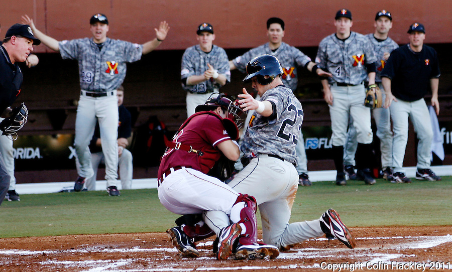 TALLAHASSEE, FL 2/18/11-FSU-VMI BASE11 CH-Florida State catcher Rafael Lopez defends home plate against Virginia Military Institute's Graham Sullivan during first inning action Friday at Dick Howser Stadium in Tallahassee. Sullivan was called out on the play. The Seminoles beat the Keydets 12-0 in the season opener for both teams..COLIN HACKLEY PHOTO