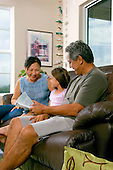 Grandparents reading to grand daughter on couch.