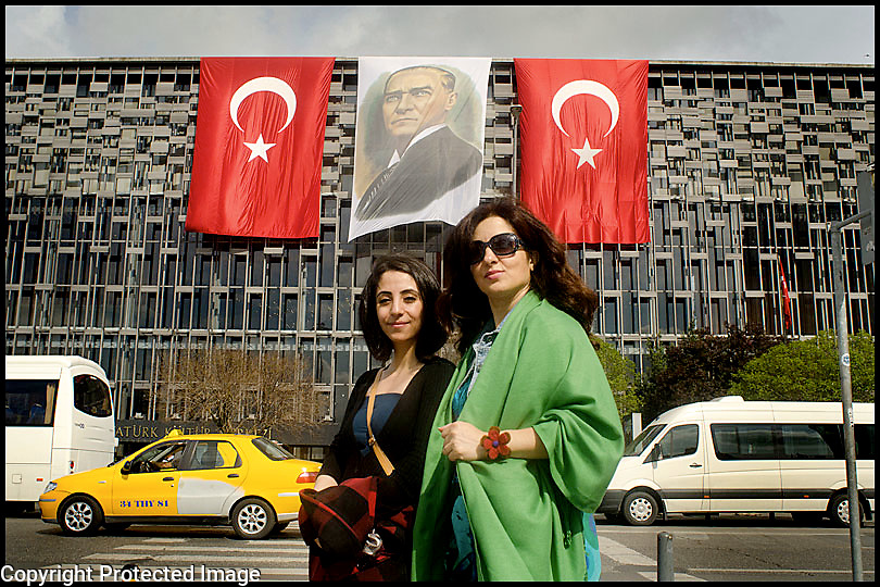 Proud Turkish Women pose in front of a portrait of Ataturk, Taksim Istanbul