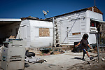 A child plays near an abandoned trailer in St. Anthony's trailer park in Mecca, Calif., March 9, 2012.