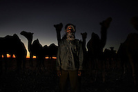 Lahbieb Embarek Ahmed, 47, camel worker. Pictured in the desert near the Saharawi refugee camps, Algeria: 'I was born in Farsia in 1962. The only thing I know is camels. I have lived with camels and they have lived with me and that's all I know. There are a lot of uses for the camels, we don't only drink their milk or eat the meat but we use it as a cure.We add oils from the camel to the milk and drink it for some diseases. If they are sick I know how to treat them. If the camel doesn't want to eat I take a lizard and mix it with some plants and feed them it. The camel is a good friend to the human, when you are alone in the desert you have no friends but there you learn how to be friends with him. They can smell their owners and know their smells, when there is something between you and the camel he will come to you and you can touch him easily and he will sit down easily. I am working with these camels for Ramadan, we will kill all of them for the Saharawi people to eat and celebrate the end of Ramadan.'.