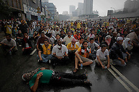 """Supporters of the """"Bersih"""" electoral reform coalition sit on the road as police approach them during clashes in downtown Kuala Lumpur July 9, 2011. Malaysian police fired tear gas and detained more than 500 people in the capital on Saturday in a bid to prevent thousands of anti-government protesters from putting on a massive show of strength against Prime Minister Najib Razak.  REUTERS/Damir Sagolj (MALAYSIA)"""