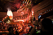 Tourists take photo of a giant dragon during a light show at a luxury hotel in Central Macau, China.