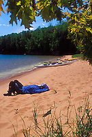A sea kayaker naps on the sand beach of Stockton Island in Apostle Islands National Lakeshore near Bayfield, Wis.
