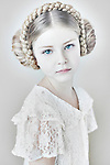 Girl with plaits in her her wearing white lace looking at camera