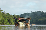 The Marowijne River, Suriname.  A small pontoon boat dredging the bottom of the river for gold.