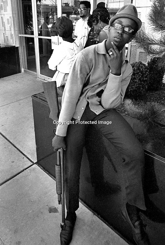 Seventeen year old Black Panther Bobby Hutton with shotgun in front of the Oakland Police Dept. (1967). Hutton was shot and killed in a shootout with Oakland Police on April 6, 1968) (photo copyright@ 1989 by Ron Riesterer)