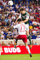 David Horst (12) of the Portland Timbers goes up for a header with Tim Cahill (17) of the New York Red Bulls. The New York Red Bulls  defeated the Portland Timbers 3-2 during a Major League Soccer (MLS) match at Red Bull Arena in Harrison, NJ, on August 19, 2012.