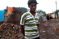 Arshad Ansari (20) lives in Bokapahari. He had to abandon his old house as the mine fire destroyed it completely. A huge coal mine fire is engulfing the city of Jharia from all its sides. All scientific efforts gone in vain to stop this raging fire. This fire is affecting lives of people living in and around Jharia. Jharkhand, India. Arindam Mukherjee