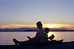 Mother and daughter having a picnic at the beach reading books at sunset, Edmonds, Washington State USA.