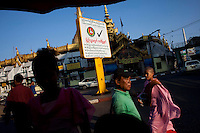 People pass an election poster, near a Buddhist temple, for the government-backed USDP (Union Solidarity and Development Party) in the old capital Rangoon (Yangon) prior to Burma's first multi-party election since 1990. However, the main pro-democracy party, the NLD (National League for Democracy), boycotted the poll and other opposition groups have alleged widespread voting fraud.