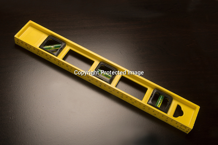 Yellow carpenter's level on a black surface.
