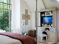 A plasma screen is concealed in a limewashed cabinet against a wall in the master bedroom