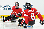Marc Dorion (7) celebrates his goal with Jeremy Booker (8) during 2010 Paralympic Games sledge hockey action at UBC Thunderbird Arena in Vancouver.Credit: CPC/HC/Matthew Manor.