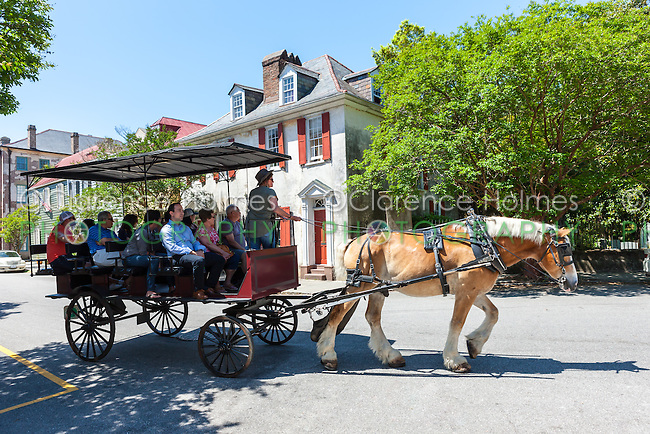 Tourists take a horse-drawn carriage tour past Antebellum homes in historic Charleston, South Carolina.