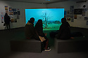 "Bristol, UK. 28.11.2015. Artists, John Wood and Paul Harrison, present ""Erdkunde: The Study of the Earth"", a new video work inspired by Bristol Museum's geology collections. The work forms part of the New Expressions 3 series of new collaborations. Picture shows: Visitors watching the video installation. Photograph © Jane Hobson."