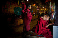 A young monk adjusts his robes as other monks sit waiting for the special prayers to start at Thiksay Monastery, Leh, Ladakh, Jammu & Kashmir, India, on the morning of 1st June 2009. Thiksay, founded in the 15th century, sits on a hill 19 km southeast of Leh town, and houses approximately 100 monks. Photo by Suzanne Lee