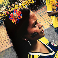 A Colombian girl, with a flag painted on her face, watches the football match between Colombia and Uruguay at the FIFA World Cup 2014, in a park in Cali, Colombia, 28 June 2014.