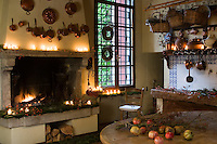 A warm fire, lit candles, berries and moss create a magical Christmas atmosphere in this rustic kitchen