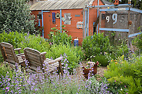 Whimsical backyard garden with edible herbs, chairs, red shed, and chickens - Amy Stewart's garden