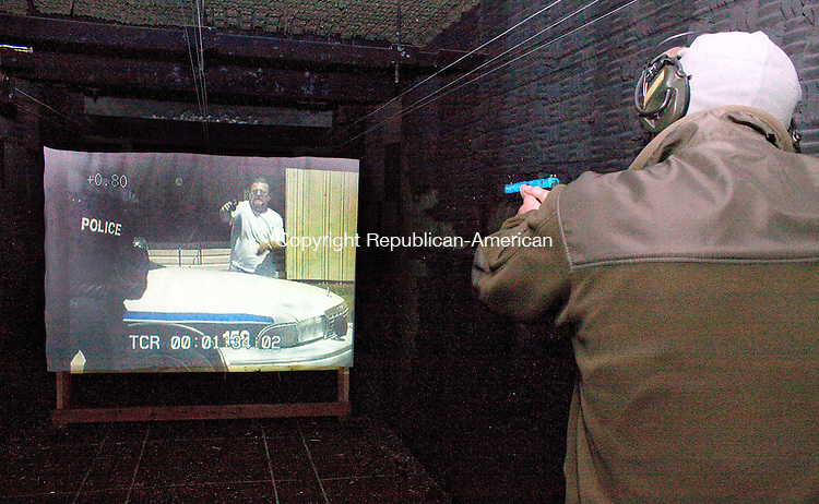 WATERBURY CT.-OCTOBER 3 2013 100313DA01- Waterbury Police Officer Stephen Alden demonstrates a scenario during a real-life video simulator that gives officers a chance to test themselves during realistic situation. <br /> Darlene Douty Republican American