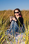 Young adult woman at beach texting and sitting on blanket in tall grass