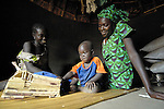 Helen Acan, right, was trained as an HIV counselor in a Church of Uganda program. Here she is visiting Betty Akwero in the Nam-Okora camp for internally displaced persons in northern Uganda. HIV rates are high among those displaced by northern Uganda's long conflict. Akwero's 2-year old son Dennis plays with a toy truck while they talk.