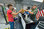 Edwin Chacon, an asylum seeker from Honduras, receives back his identification documents from Border Patrol agent Rene Perez in the Valley International Airport in Harlingen, Texas. With Chacon is Cindy Johnson, a United Methodist deaconess who drove him to the airport from the Posada Providencia in San Benito, where Chacon, 18, stayed for several days after being released by immigration authorities pending a judicial hearing on his asylum request. He was on his way to stay with a relative elsewhere in the United States.<br /> <br /> Sponsored by the Catholic Sisters of Divine Providence, the Posada Providencia provides a safe place for people in crisis from all over the world who are seeking legal refuge in the United States.
