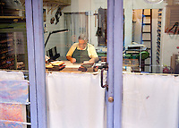 Artisan book-binder (rilegatore) Enrico Giannini at work in his small bottega on Via dei Velluti in Florence Italy.  Enrico Giannini is the fifth generation of a well known family of book-binders in Florence